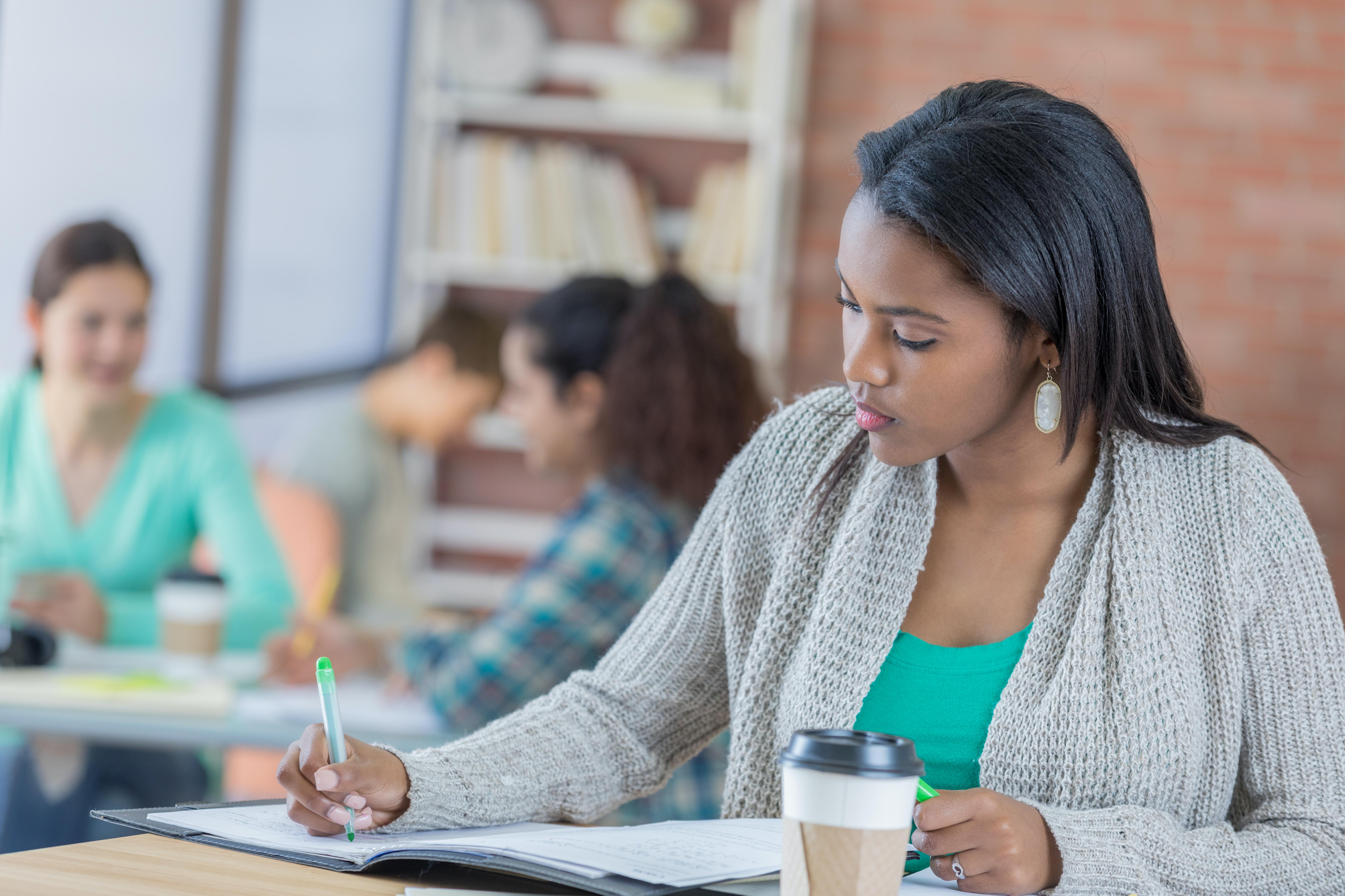 A female graduate healthcare student writes at a desk