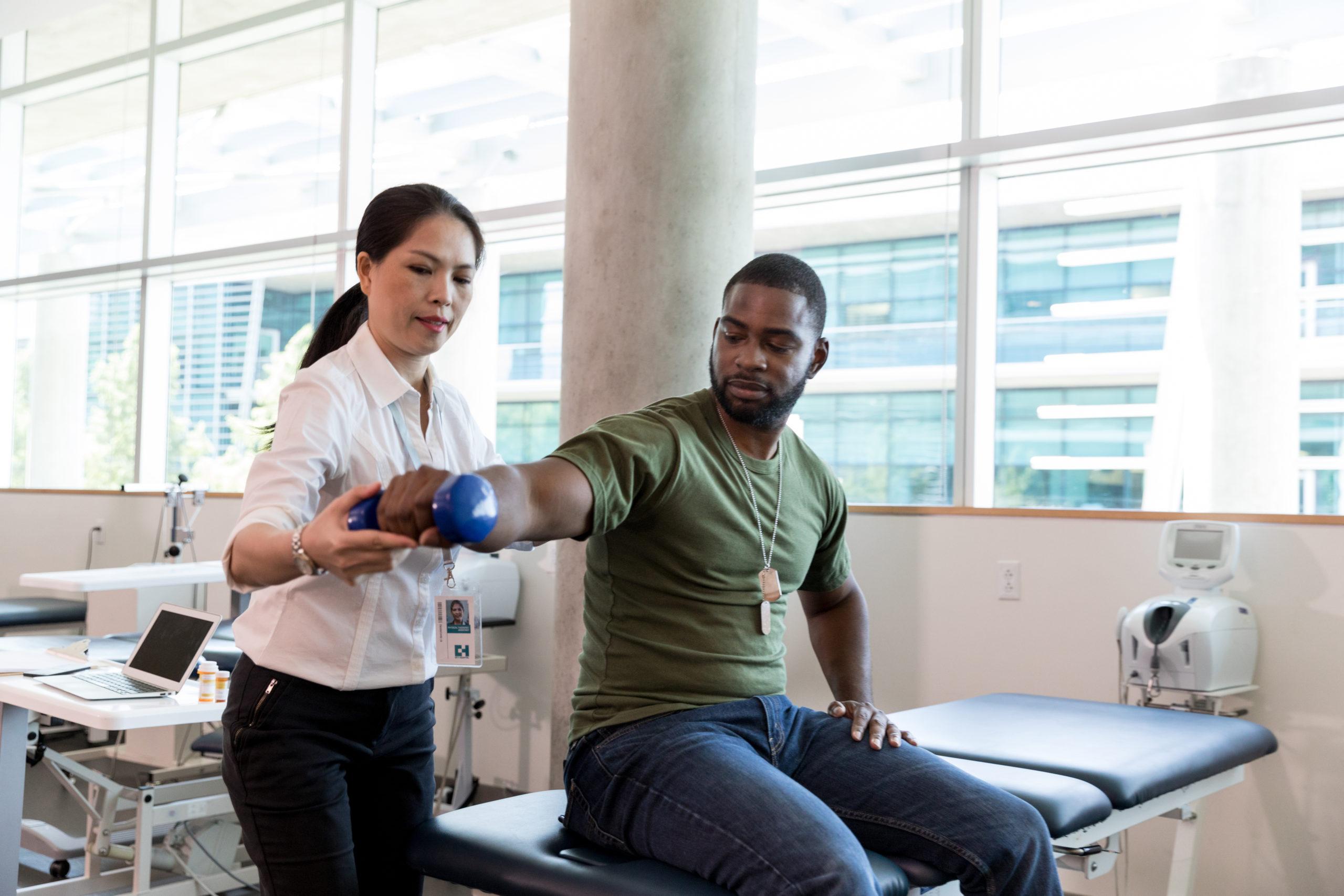 PT helps patient lift arm