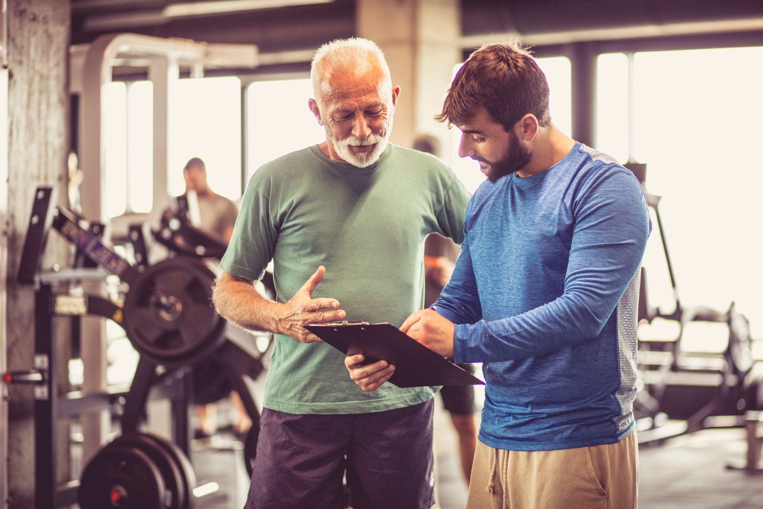 Sports performance specialist speaks with client in a gym