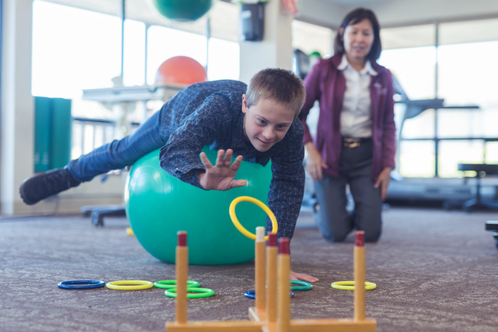 OT works with boy in clinic on exercise ball with rings