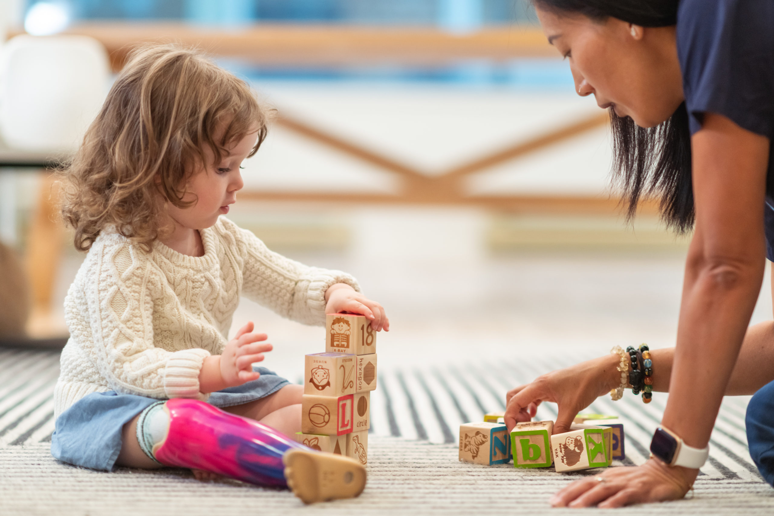 An occupational therapist with an OTD works with a young toddler girl with a prosthetic leg to stack blocks
