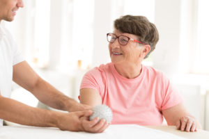 Healthcare provider with a PhD works with a patient in neurologic rehabilitation